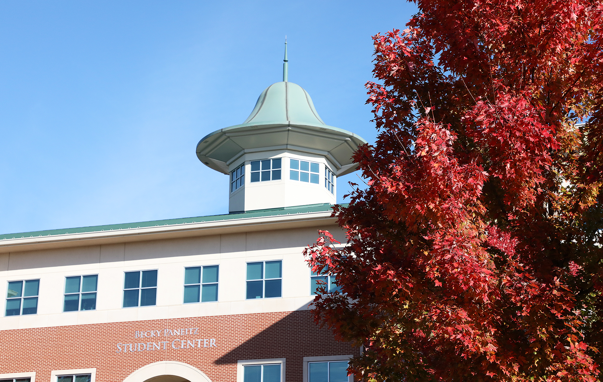 Top of the Student Center with red, fall foliage in front