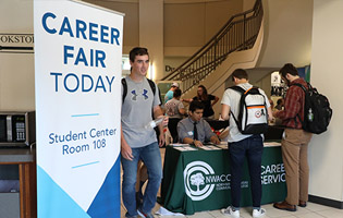 Male student walking past a career fair banner