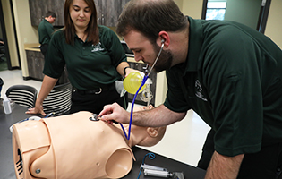 Male and female EMT students learning