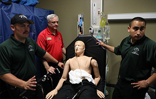 male paramedic students with dummy