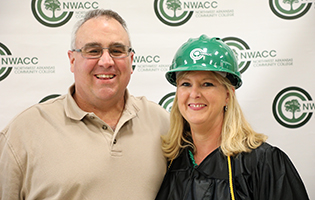 Female graduate wearing a hard hat with a man smiling