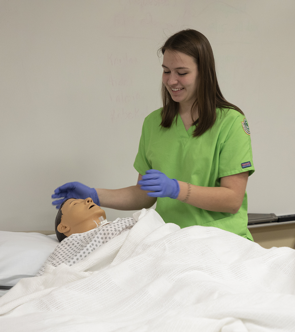 Female Early College Experience student practicing CNA skills on a dummy
