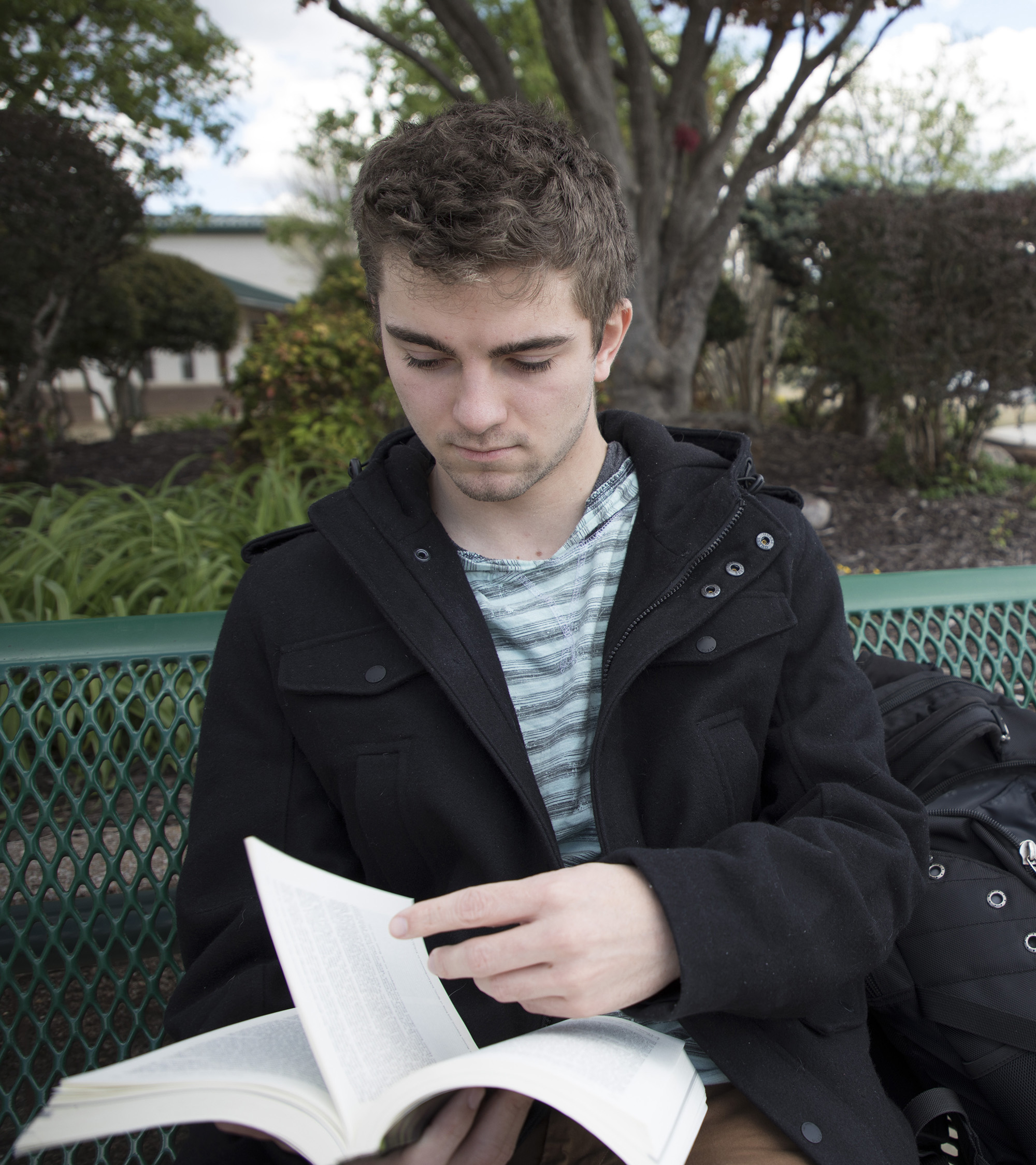Male student outside with a book