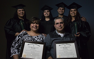 Latino family smiling and holding college degrees