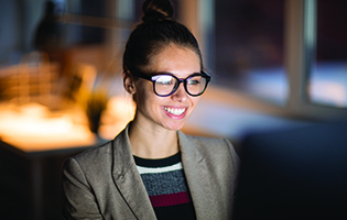 female wearing glasses smiling at computer