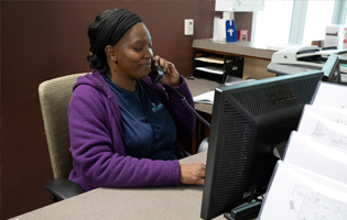 Black female sitting at a desk talking on an office phone