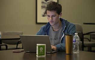 Male student working on laptop