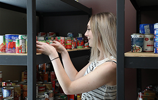 Woman stocking the food pantry shelves